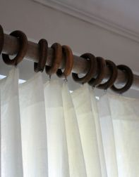 white cotton curtains with wooden rings